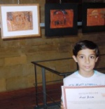 one of the young artists holding his certificate
